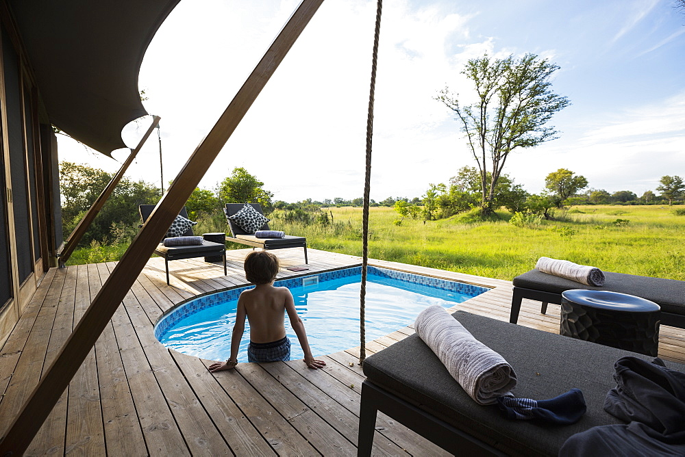A boy in a swimming pool at a safari camp, looking out over the landscape, Botswana