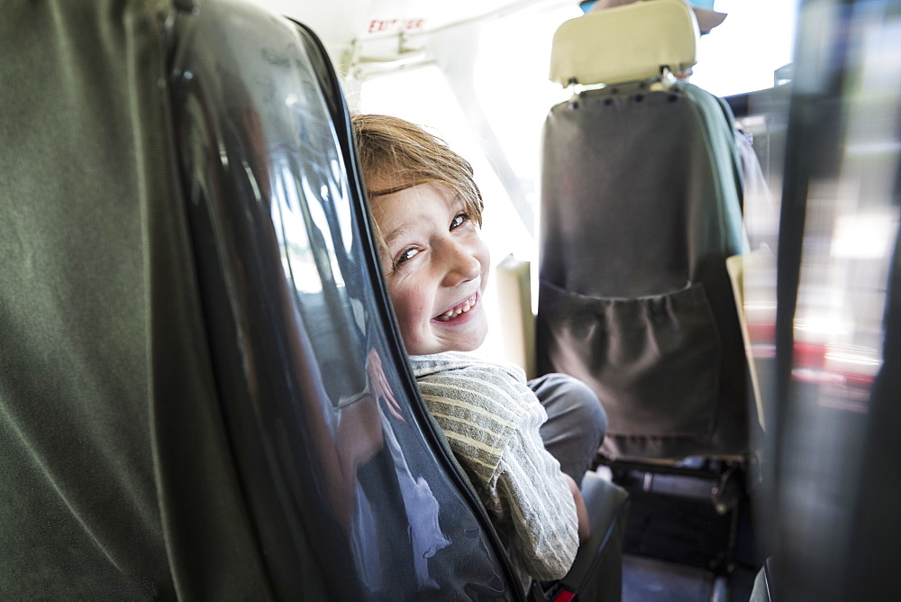 A smiling boy in a light aircraft seat, looking over his shoulder