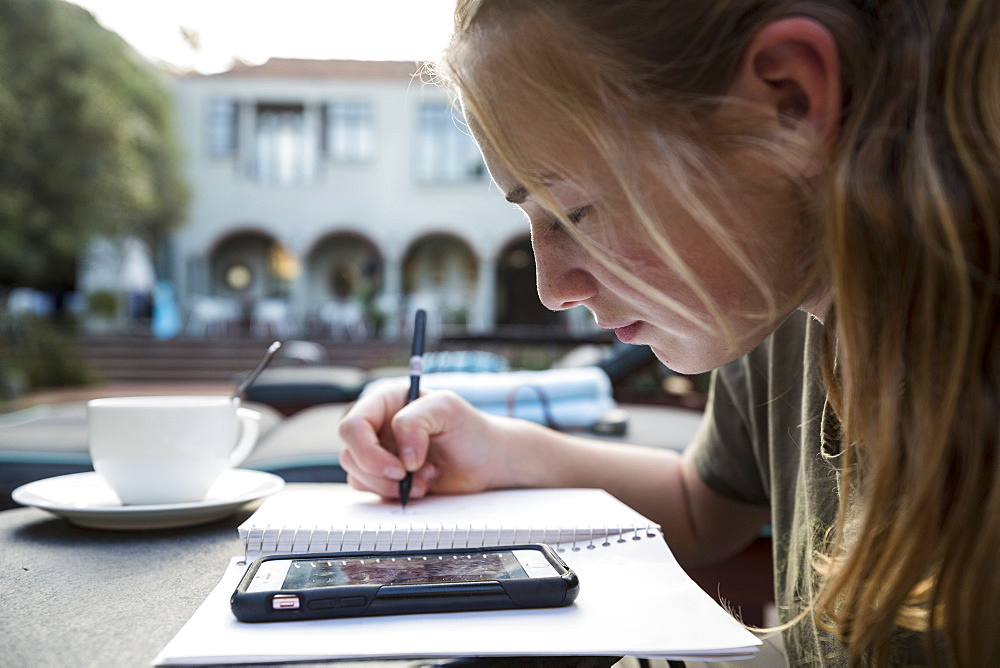 A teenage girl using pen and paper making notes, looking at a smart phone, writing a diary or doing homework
