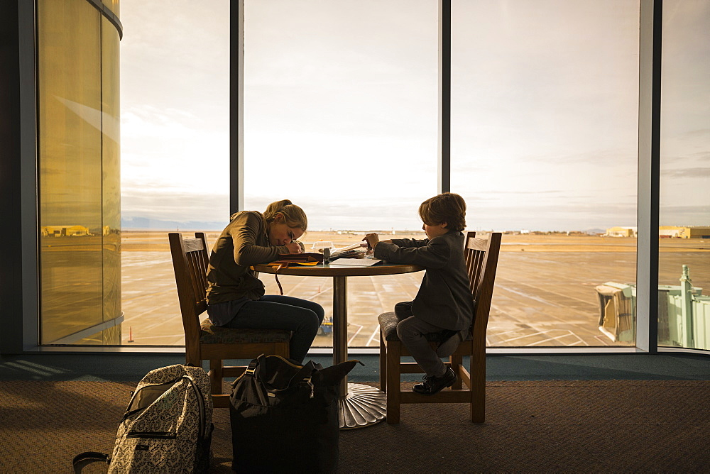 A boy and his older sister seated at a table in an airport lounge, writing and drawing