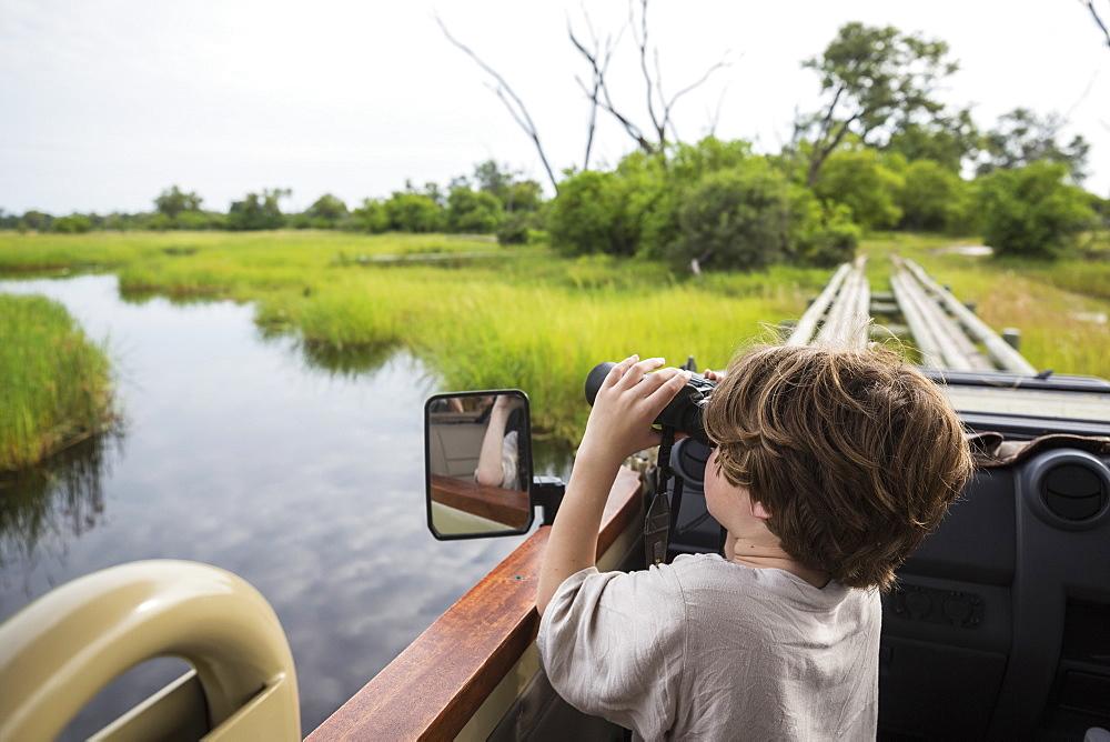 A six year old boy using binoculars looking over water from a safari vehicle, Botswana