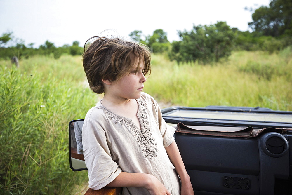 Six year old boy standing looking around the landscape in a safari jeep, Botswana