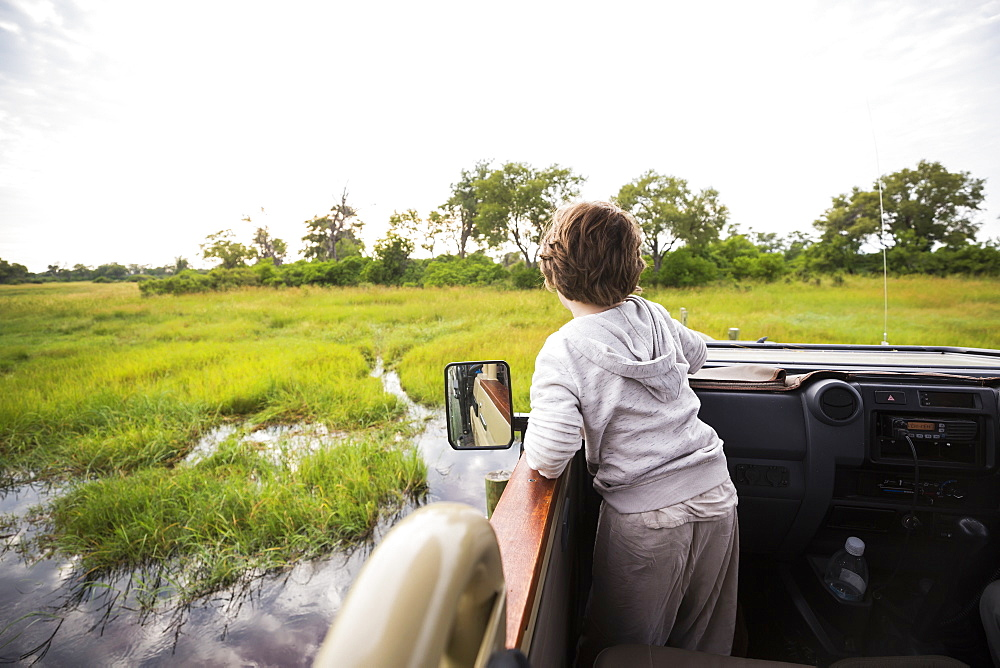 A six year old boy in a safari jeep driving through water in marshes, Botswana