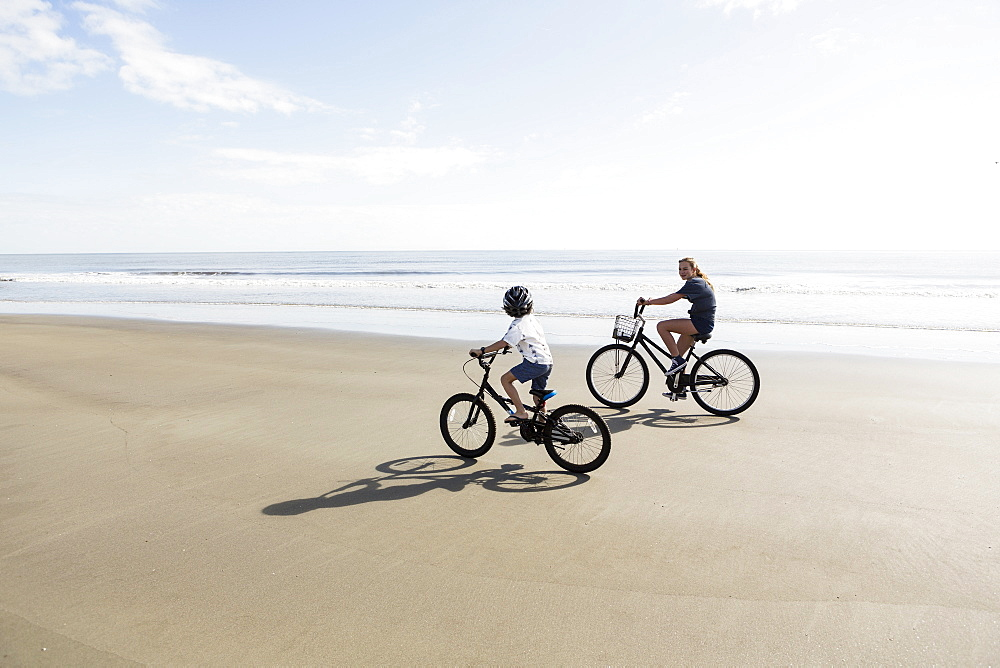 Siblings, a boy and girl cycling on a beach, United States of America