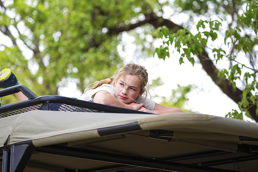 A teenage girl lying on the canopy of a safari vehicle under a tree, Okavango Delta, Botswana