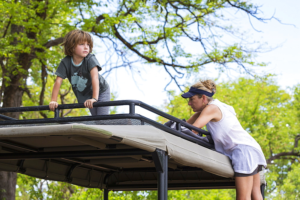 A five year old boy and a teenage girl on the observation platform of a safari jeep under trees, Okavango Delta, Botswana