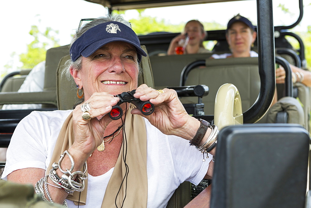A family in a safari jeep in a wildlife reserve, a senior woman with binoculars, Okavango Delta, Botswana