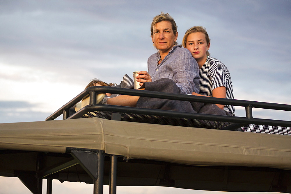 Mother and teenage daughter on top of safari vehicle looking into the distance, Okavango Delta, Botswana