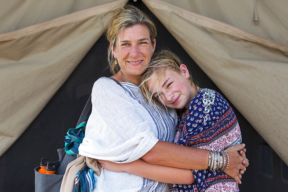 Mother and her young teenage daughter outside a tent, Okavango Delta, Botswana