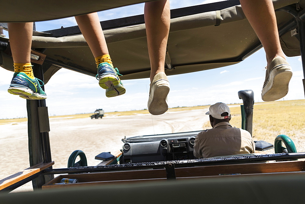 A safari vehicle, one person in the driving seat and two sets of dangling legs of passengers on the observation platform, Kalahari Desert, Botswana