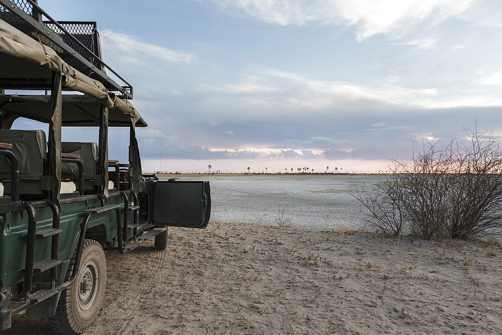 Safari vehicle with a view over the salt pan landscape, Kalahari desert