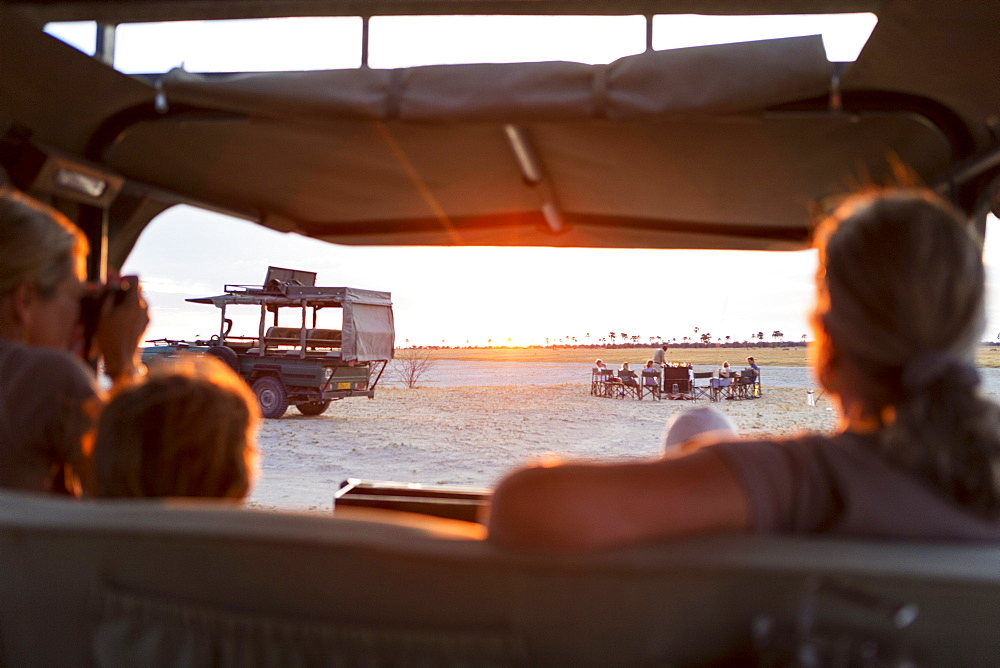 Family in safari vehicle taking photographs of a safari picnic at sunset