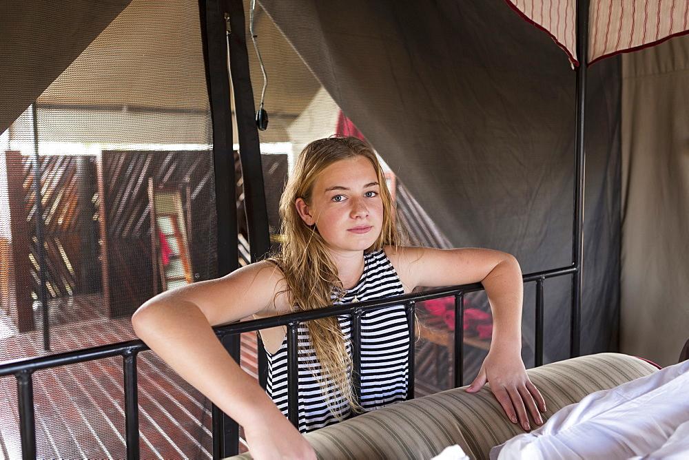 A twelve year old girl beside a bed in a tent, Kalahari Desert, Botswana
