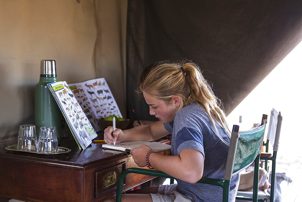 Twelve year old girl seated in a tent, writing or drawing in a journal