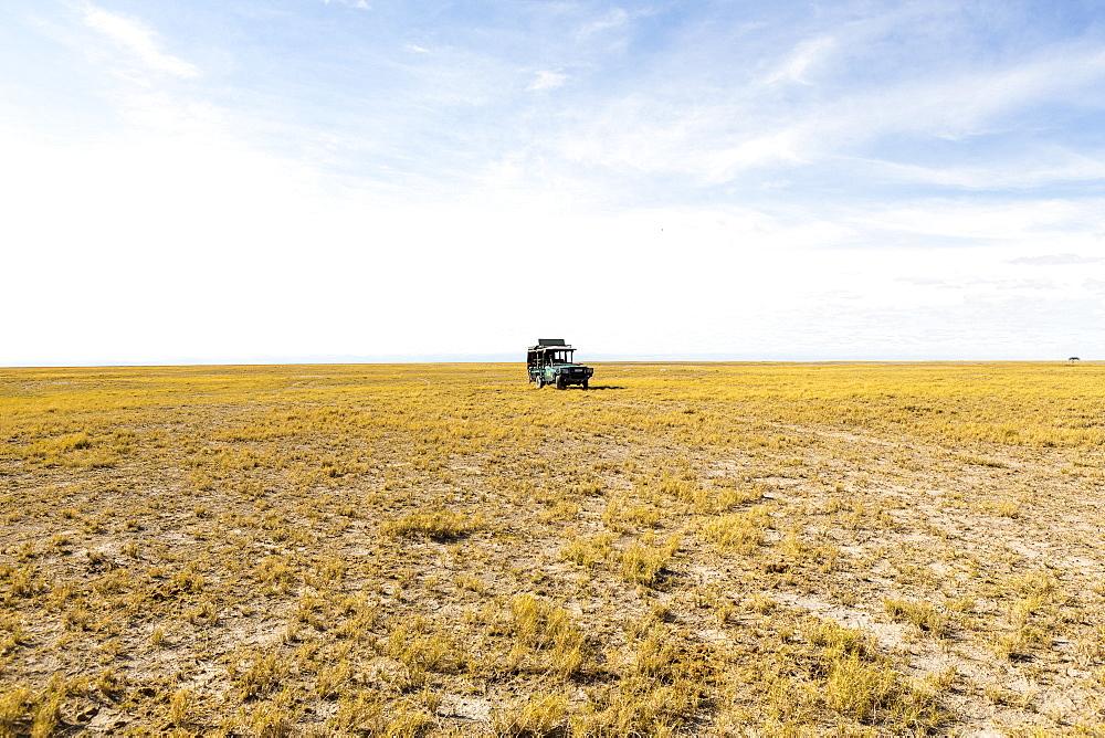 A safari vehicle on open ground in the desert