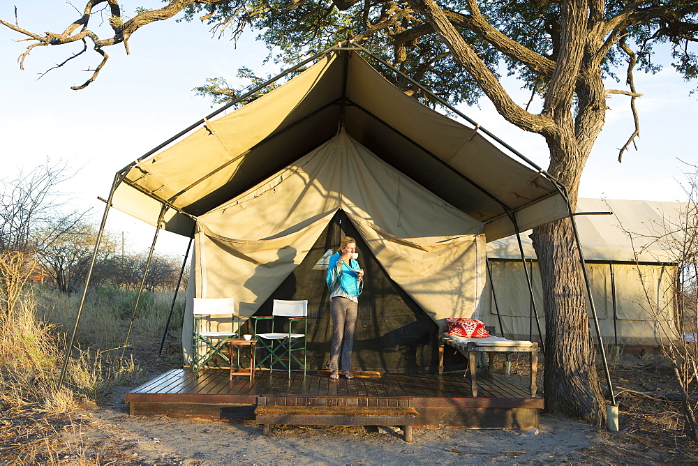 A young girl outside her tent at a wildlife reserve in the Kalahari Desert