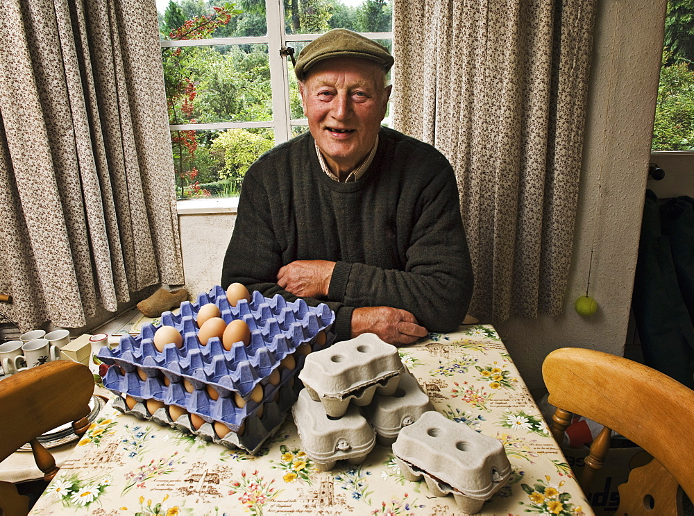 A farmer seated at a table in a farmhouse with trays of fresh eggs, Gloucestershire, England