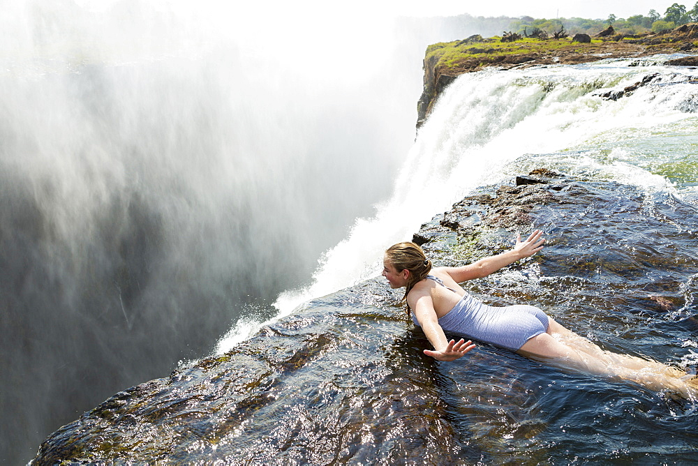 Young girl in the water at the Devils Pool lying on her front, arms spread out, at the edge of the cliff of Victoria Falls, Zambia