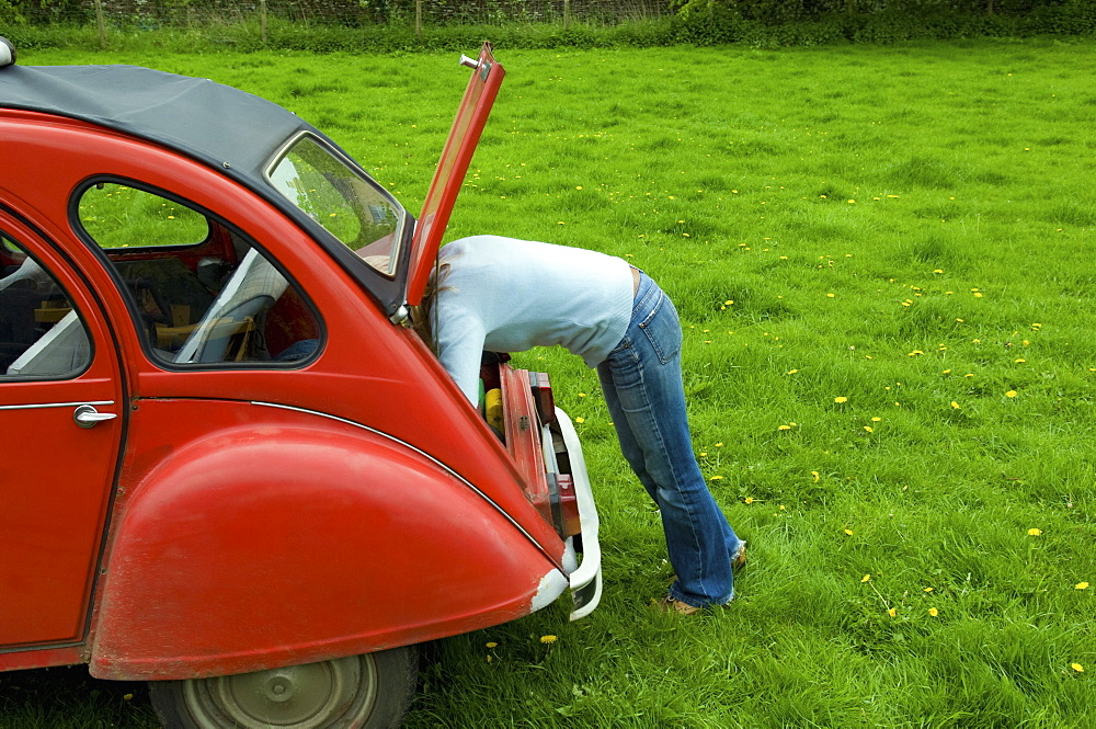A person leaning in to the boot at the rear of the car, Gloucestershire, England