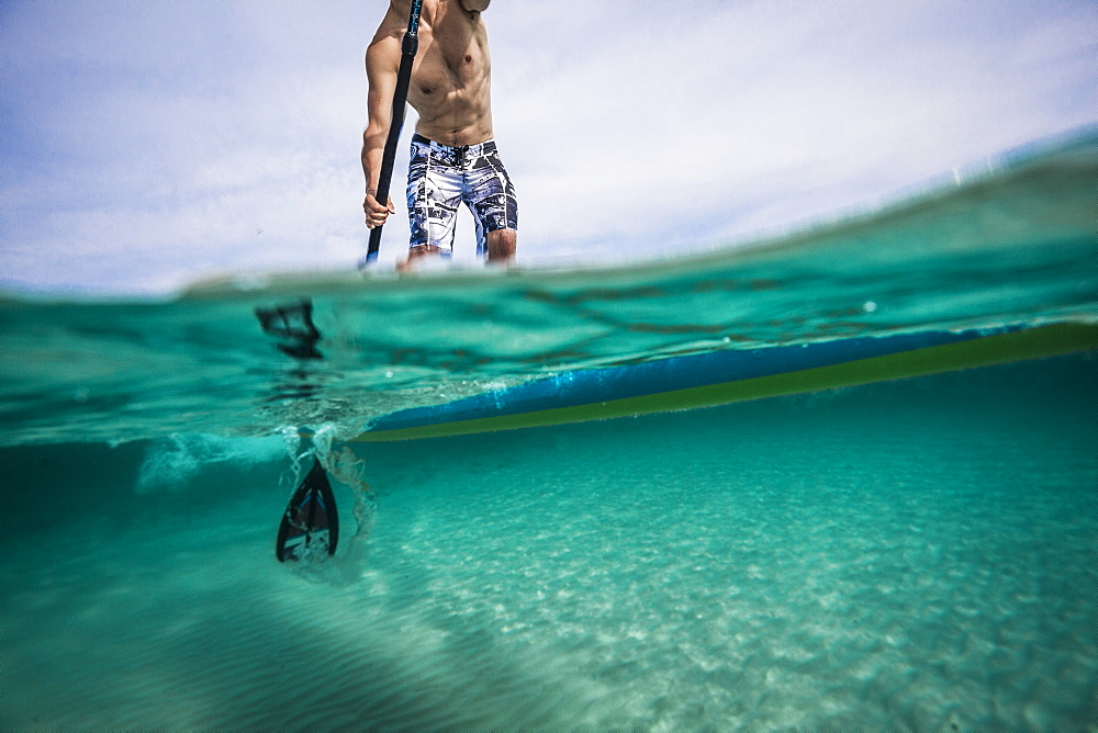 A shot of a person on a paddleboard both underwater and above the surface