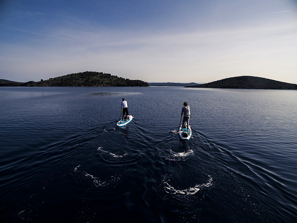 High angle shot of two people on paddleboards