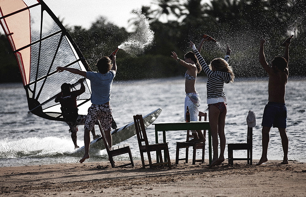 Small group of men and women standing on a sandy beach around table and chairs, arms raised, holding bottles, watching a windsurfer