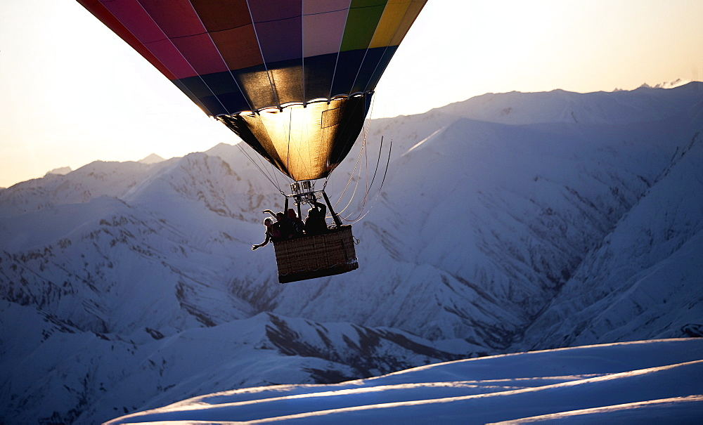 People in a hot air balloon mid air over a snow covered mountain