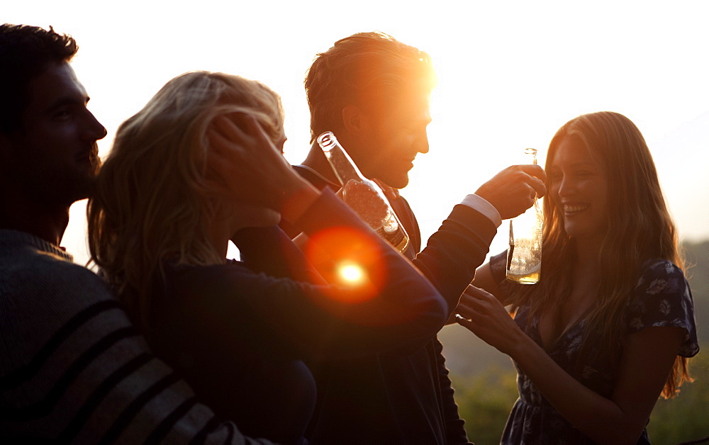 Two men and two women standing outdoors at sunset, holding beer bottles, smiling