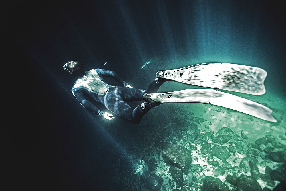 High angle underwater view of diver wearing wet suit and flippers, sunlight filtering through from above, United States of America