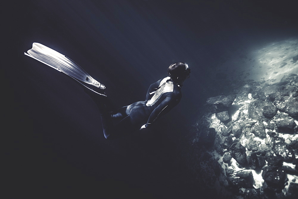 Underwater view of diver wearing wet suit and flippers, diving near rocks, United States of America
