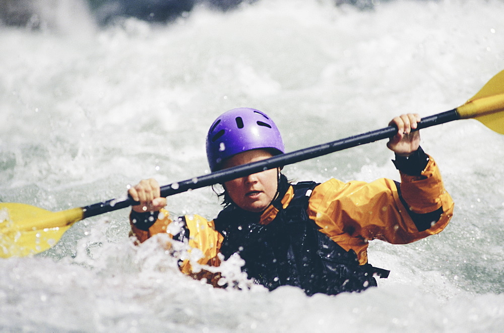 Female whitewater kayaker paddling rapids and surf on a fast flowing river