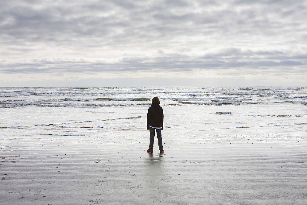 Teenage boy standing on vast beach waves and overcast sky in distance, Olympic National Park, Washington, United States of America
