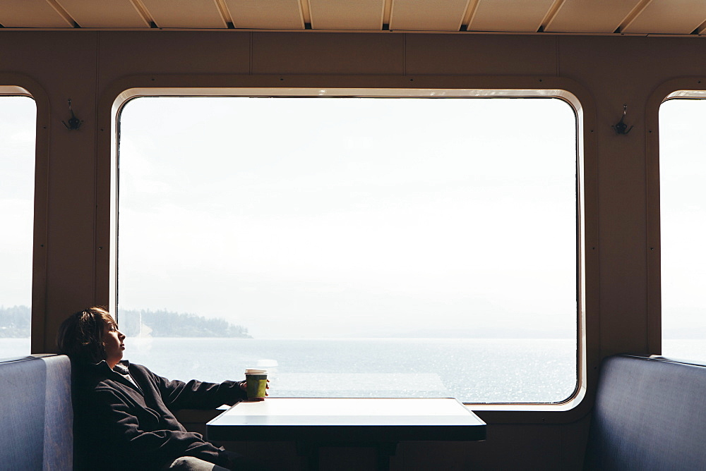 Teenage boy sitting on ferry looking out of a window