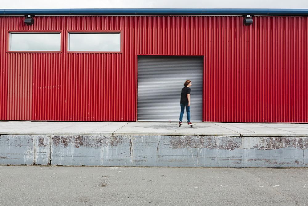 Teenage boy skateboarding in front of industrial warehouse loading zone - 1174-8924