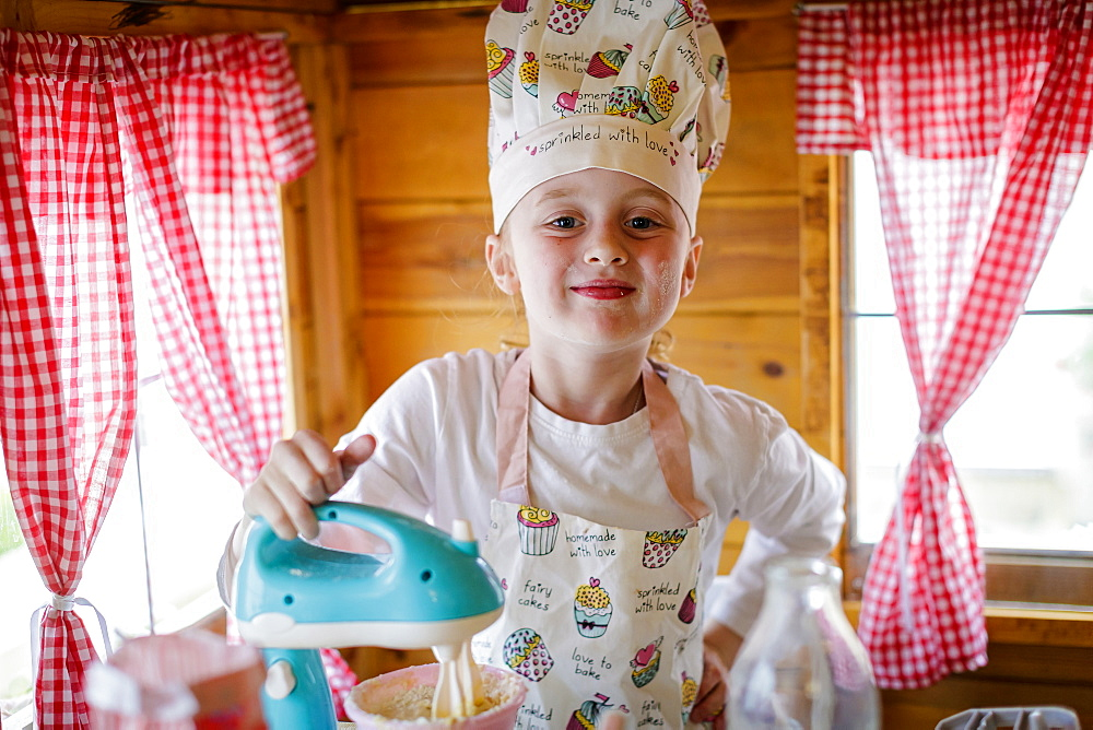 Portrait of young girl dressed in chef's outfit in wendy house pretending to cook in kitchen