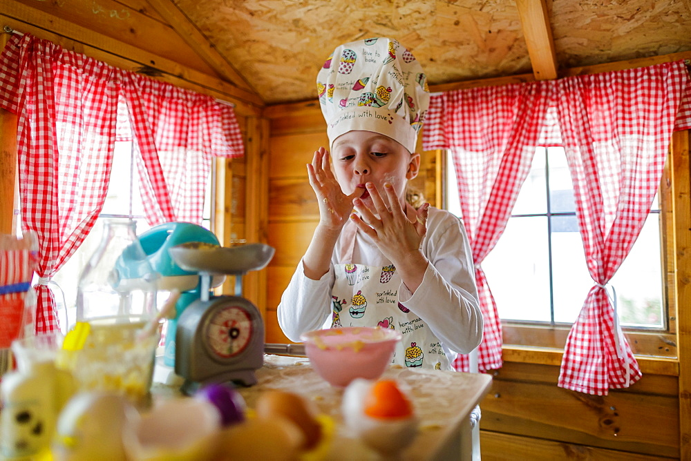 Young girl in wendy house liking fingers pretending to cook in kitchen