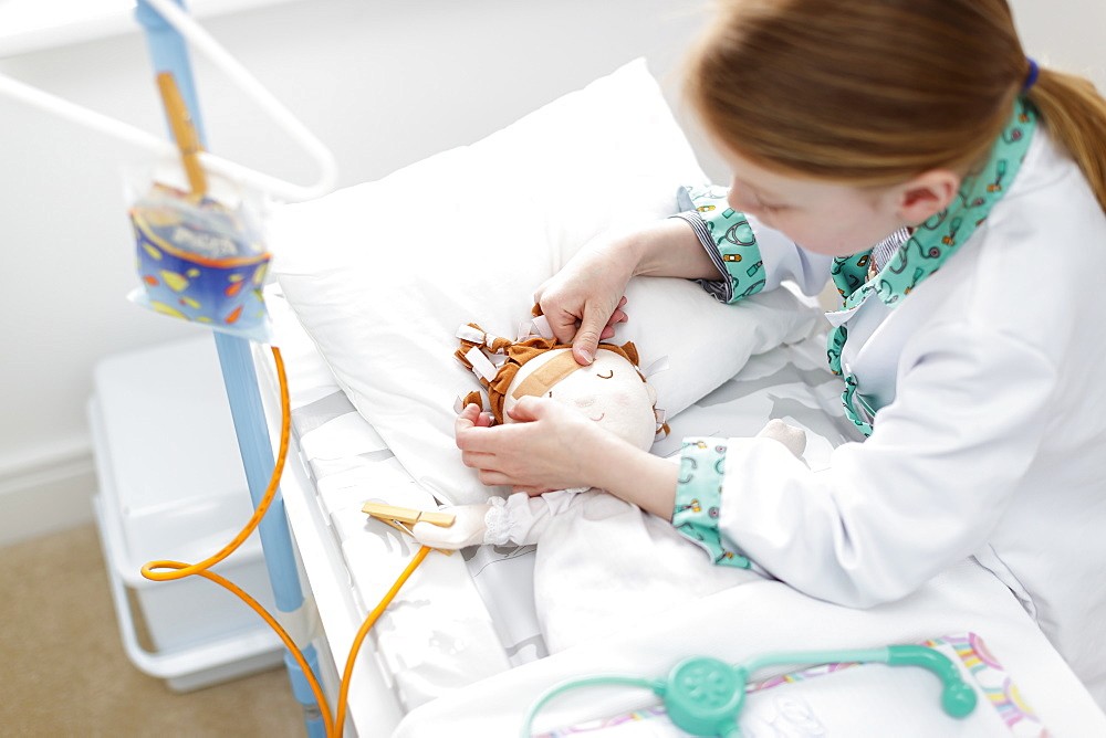 Young girl dressed as doctor putting plaster on doll's head in make-believe hospital bed - 1174-8938