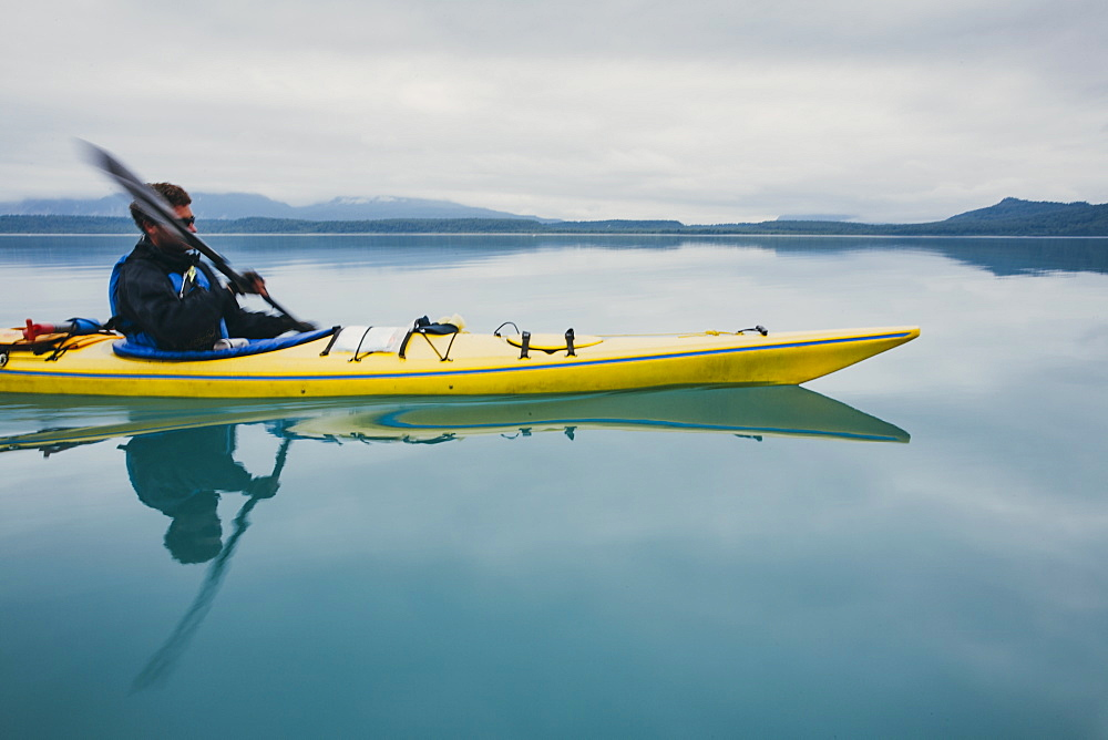 Man sea kayaking inan inlet on the, Alaska coastline