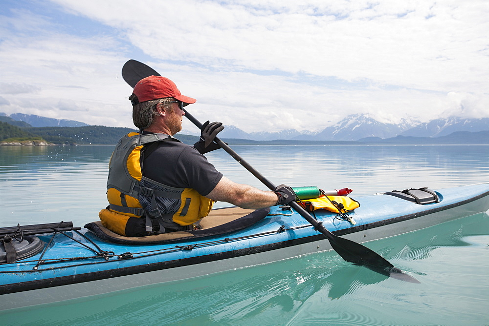 Man sea kayaking calm waters of an inlet in a national park - 1174-8948