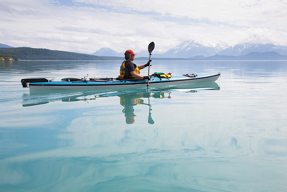 Man sea kayaking calm waters of an inlet in a national park - 1174-8949
