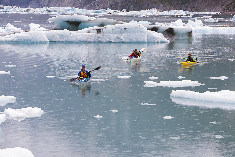 Sea kayakers paddling in glacial lagoon at a glacier terminus on the coast of Alaska