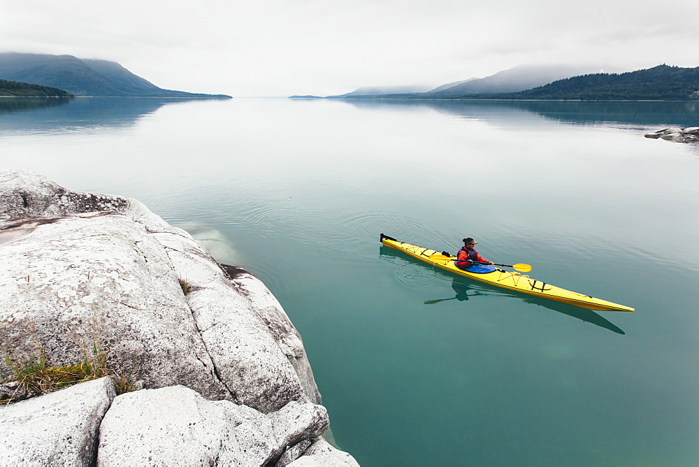 Female sea kayaker paddling pristine waters of Muir Inlet overcast sky in distance, Glacier Bay National Park, Alaska