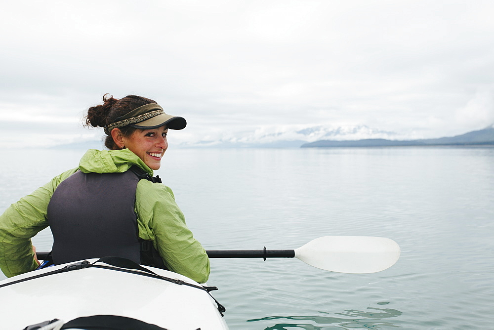 Happy female woman sea kayaking pristine waters of Muir Inlet, Glacier Bay National Park and Preserve, Alaska