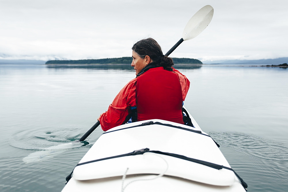 A middle-aged woman paddles sea kayak in the pristine waters of Muir Inlet, Glacier Bay National Park and Preserve, Alaska