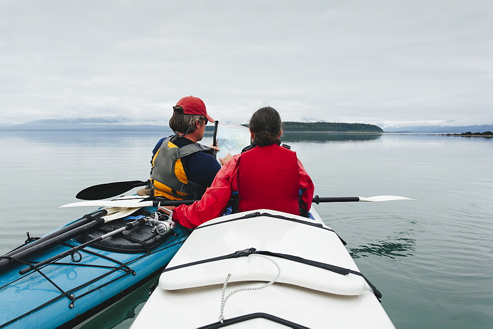 Sea kayakers looking at nautical chart and mapan inlet on the, Alaska coastline
