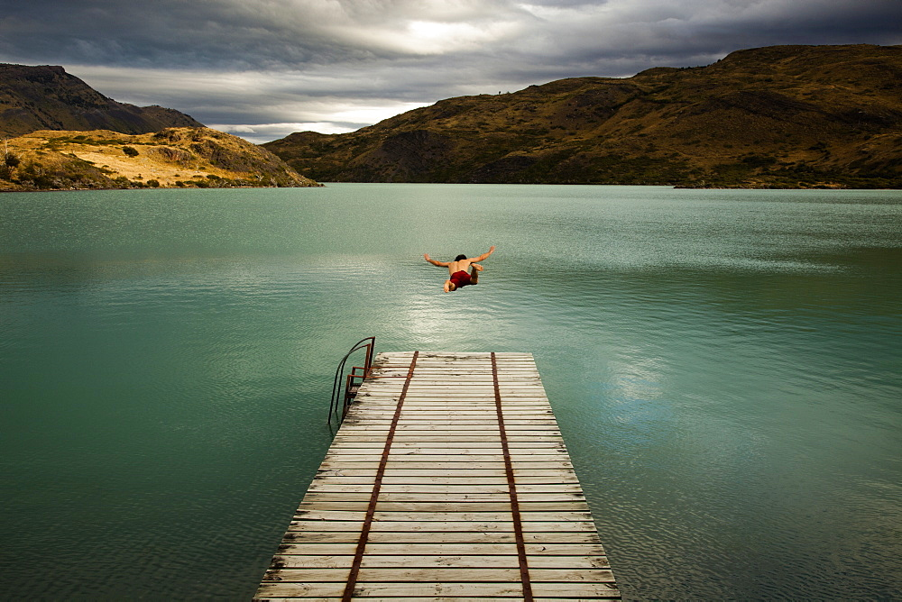A young man in mid air, diving off a wooden pier, into calm lake surrounded by mountains in Torres del Paine National Park, Chile, Torres del Paine National Park, Chile.