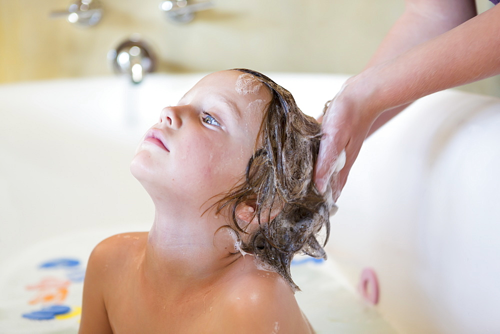 4 year old boy having a bath and shampoo in bath tub