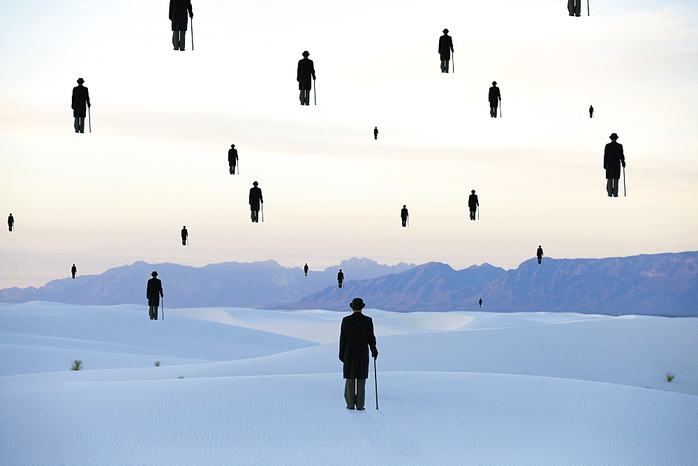 Men in bowler hats with umbrellas outline of figures floating above ground in a sand dune desert