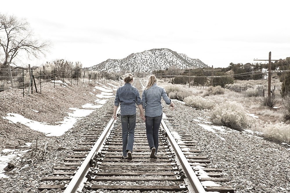 pre teen girl friends walking railroad tracks together, New Mexico - 1174-9003