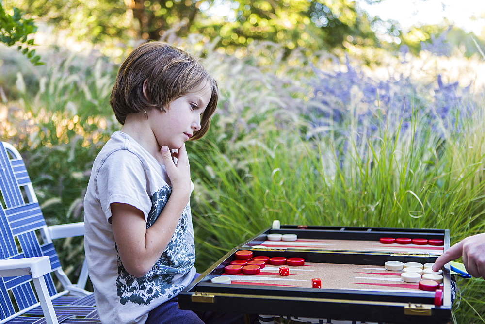 A young boy playing backgammon outdoors in a garden, New Mexico, United States - 1174-9021